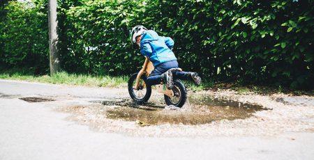 Kind in einem Helm für einen Fahrradanhänger